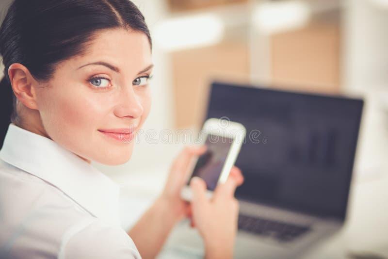 Коммерсантка посылая сообщение с smartphone в офисе Коммерсантка стоковое фото rf
