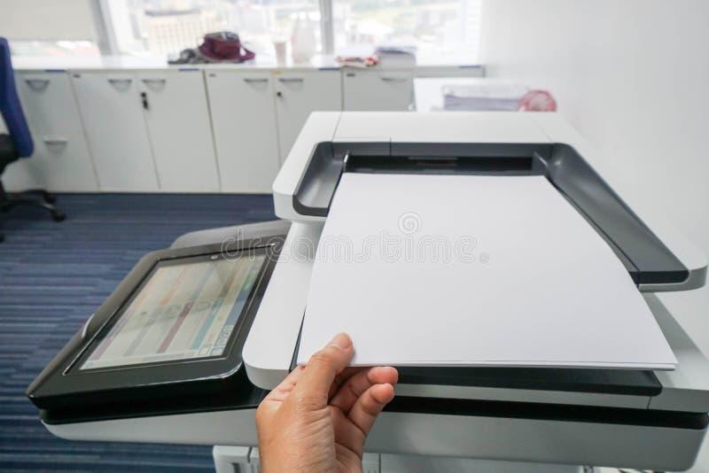 Коммерсантка положила насмешливый поднимающий вверх лист бумаги A4 на питание принтера стоковое фото rf