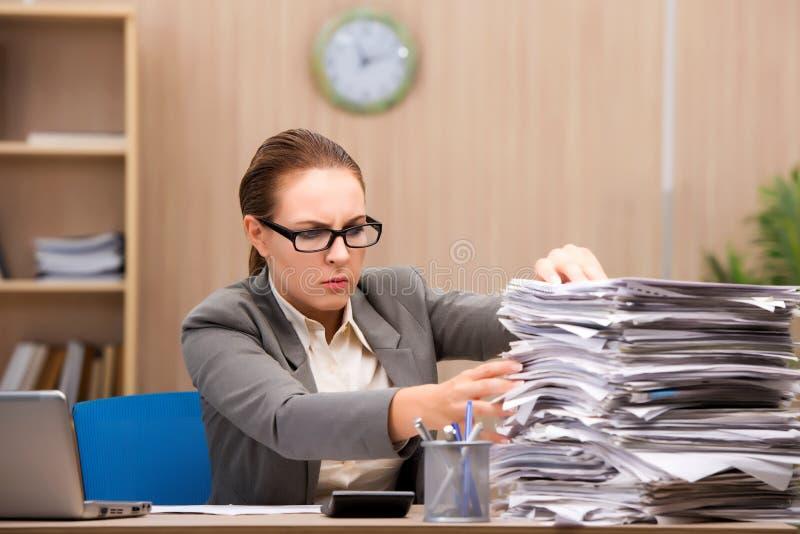 Коммерсантка под стрессом от слишком много работы в офисе стоковые изображения
