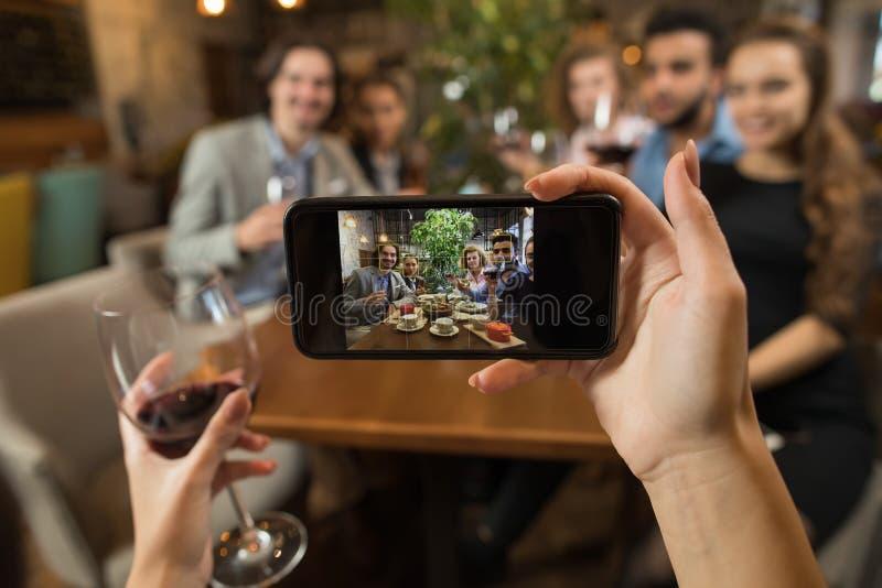Коммерсантка принимая Selfie молодые бизнесменов таблица ресторана вина питья группы сидя, Clink стекел владением друзей стоковое фото rf
