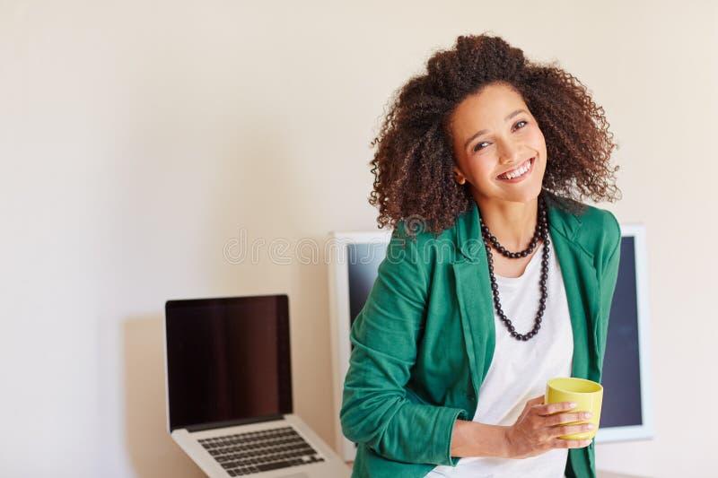 Коммерсантка при вьющиеся волосы держа чашку кофе стоковое изображение rf
