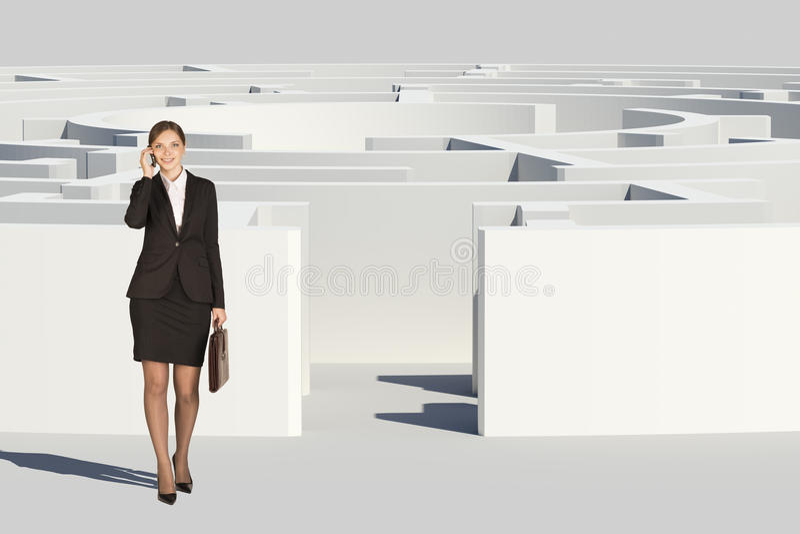 Коммерсантка при чемодан идя вне лабиринт стоковое фото rf
