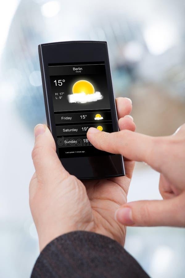 Коммерсантка проверяя прогноз погоды на smartphone стоковая фотография rf