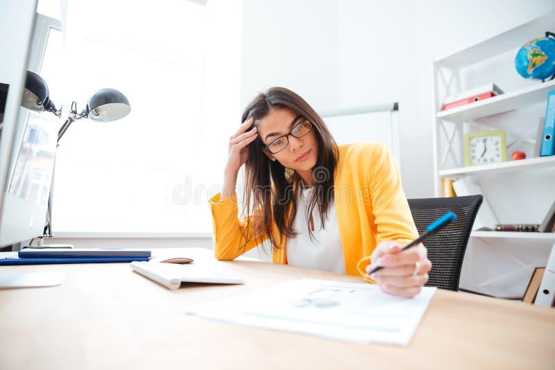 Коммерсантка работая на ее рабочем месте в офисе стоковое изображение