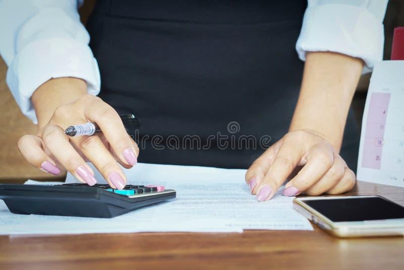 Коммерсантка работая на калькуляторе с мобильным телефоном стоковые фотографии rf
