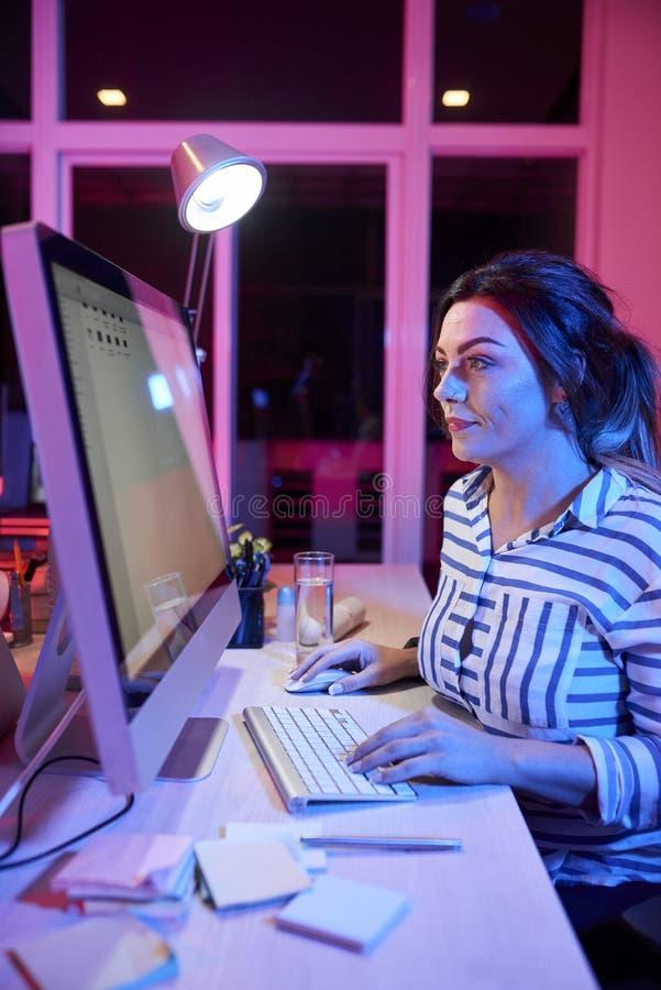 Коммерсантка работая на компьютере до ночи стоковое изображение rf