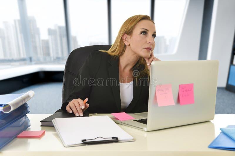 Коммерсантка работая на портативном компьютере сидя на запомненном отсутствующем стола стоковая фотография