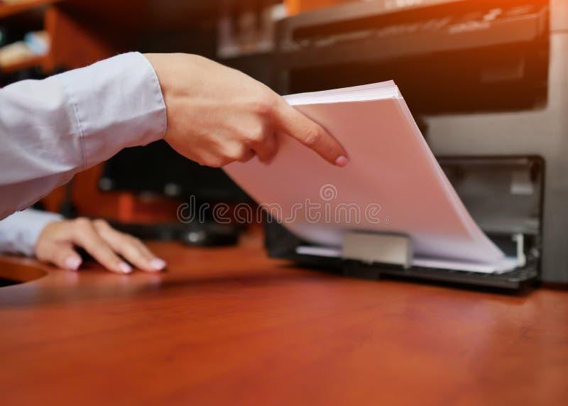 Коммерсантка работая с принтером в офисе стоковое изображение