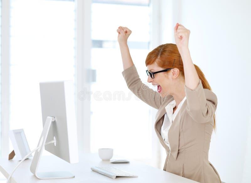 Коммерсантка радованнсяая в ее офисе стоковое фото rf
