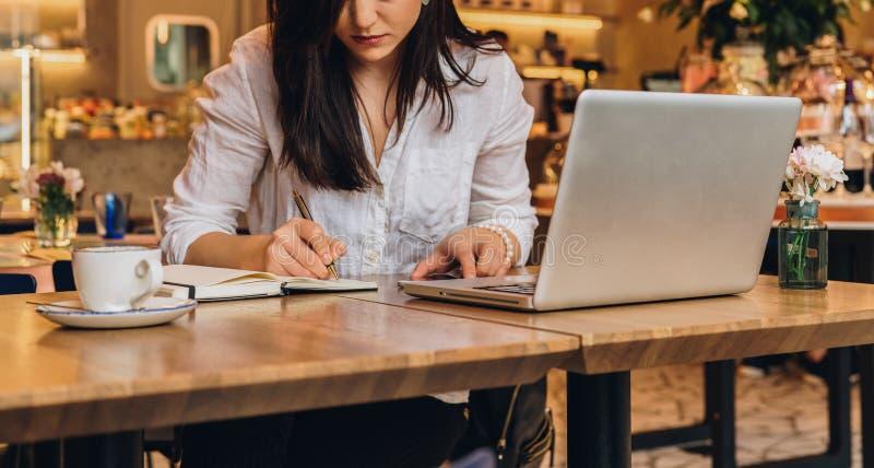 Коммерсантка сидит в кафе на таблице перед компьтер-книжкой, делающ примечания в тетради, работая Учить студента онлайн стоковое изображение