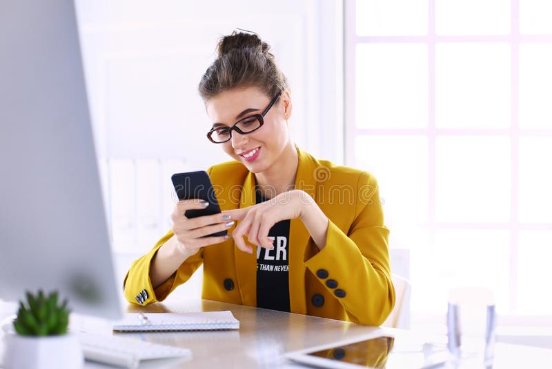 Коммерсантка сидя в офисе с ноутбуком на телефоне стоковое фото rf