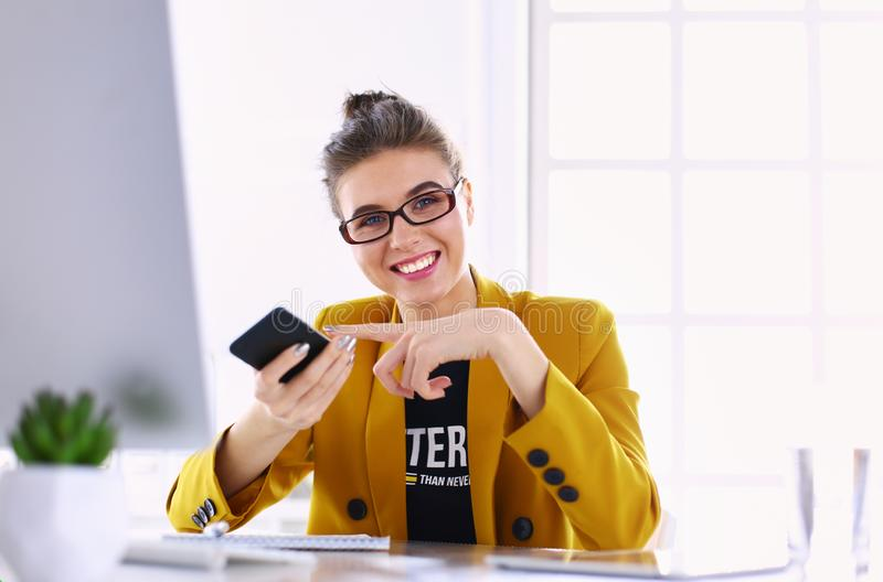 Коммерсантка сидя в офисе с ноутбуком на телефоне стоковые фотографии rf