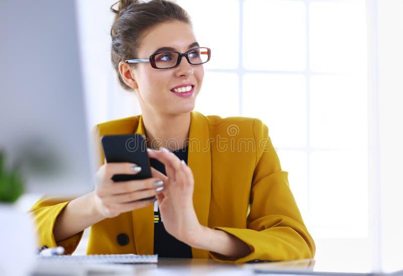 Коммерсантка сидя в офисе с ноутбуком на телефоне стоковые фото