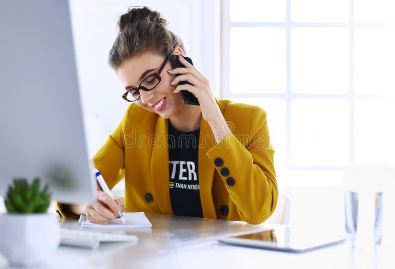 Коммерсантка сидя в офисе с ноутбуком на телефоне стоковая фотография