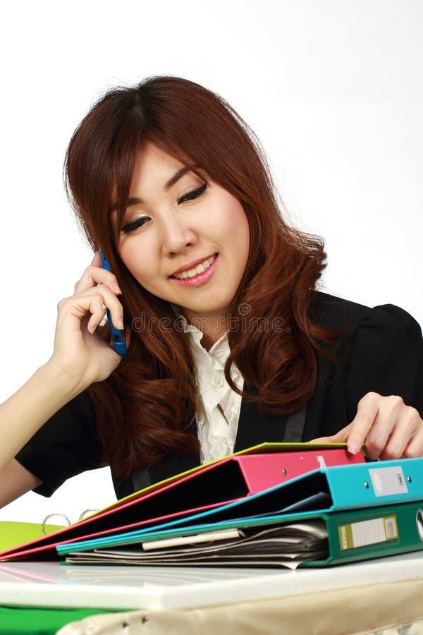 Коммерсантка сидя используя мобильный телефон стоковые фото