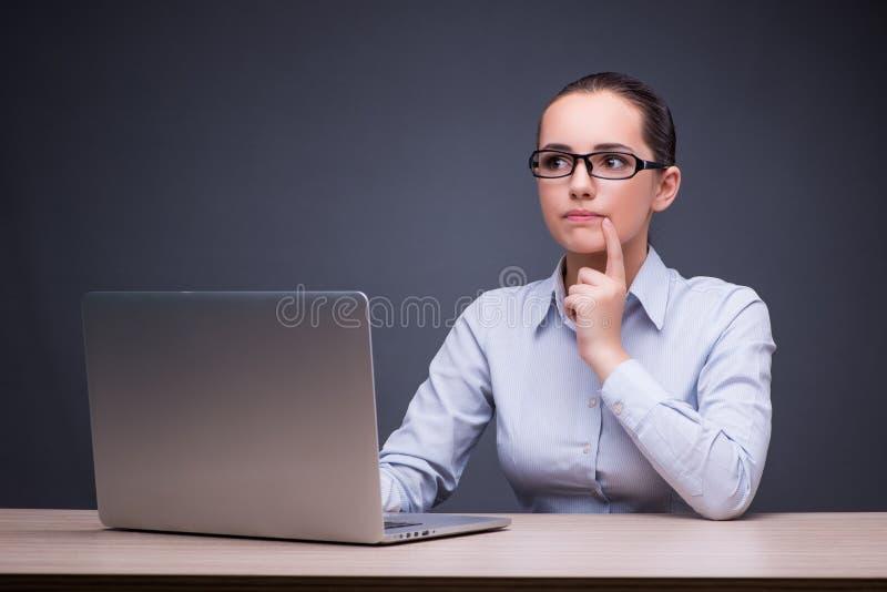 Коммерсантка сидя на ее столе в концепции дела стоковая фотография