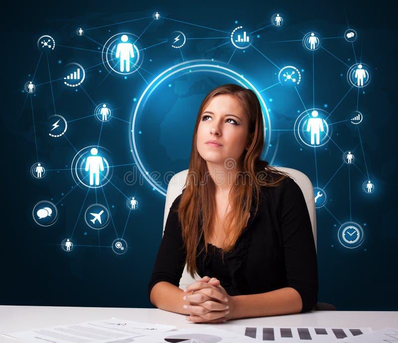 Коммерсантка сидя на столе с социальными иконами сети бесплатная иллюстрация