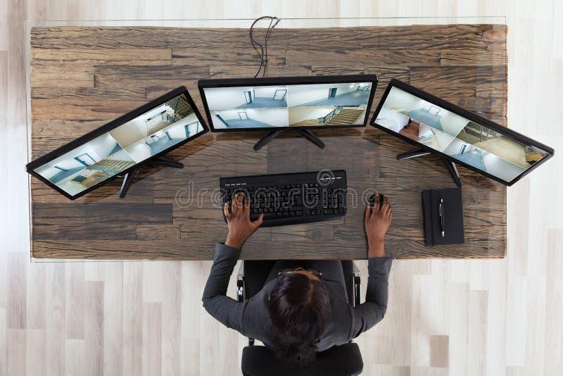 Коммерсантка смотря множественный отснятый видеоматериал камеры в офисе стоковое фото