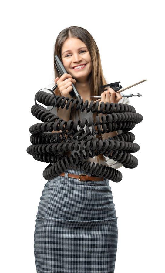 Коммерсантка стоит связанной большим черным шнуром металла и канцелярские товары удержания стоковое фото