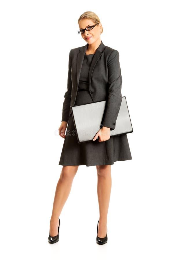 Коммерсантка стоя и держа компьтер-книжка стоковое фото rf