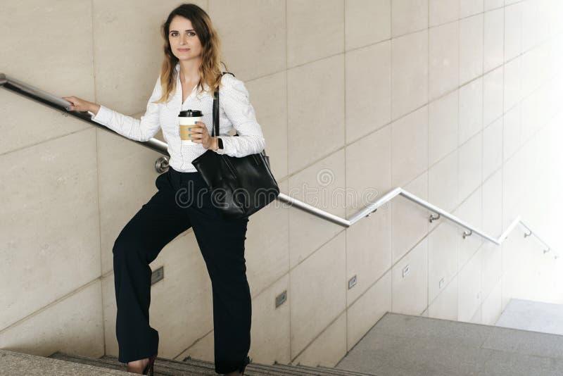 Коммерсантка стоя на лестницах стоковые фото