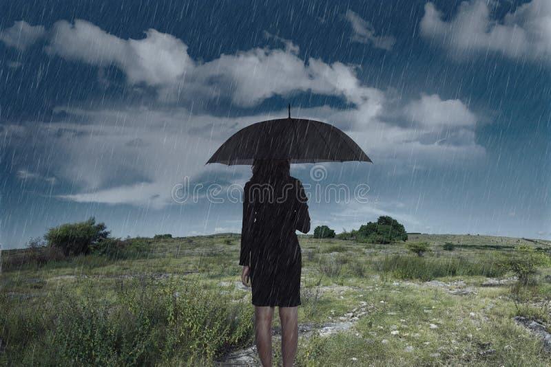 Коммерсантка стоя с зонтиком в дожде стоковые изображения rf