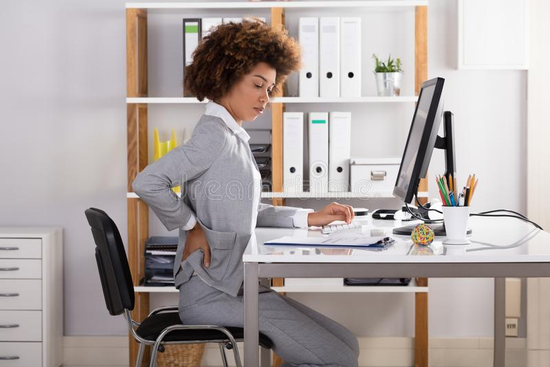 Коммерсантка страдая от боли в спине стоковые фотографии rf
