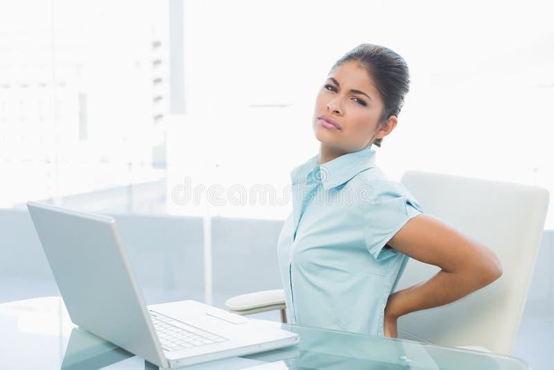 Коммерсантка страдая от задней боли в офисе стоковые изображения