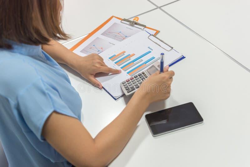 Коммерсантка с бумагами и калькулятором стоковое фото