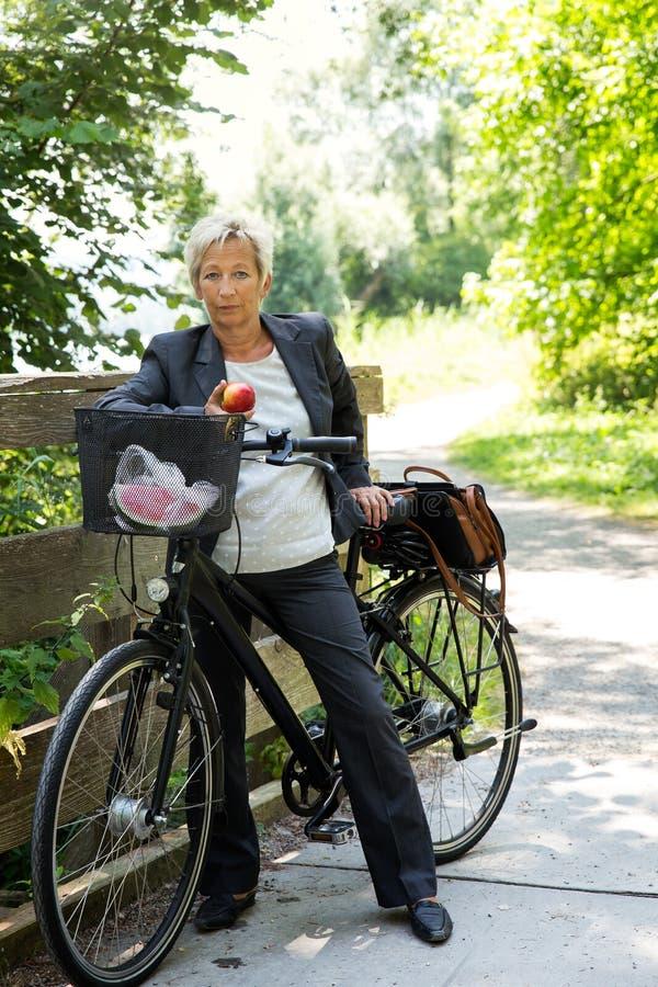 Коммерсантка с велосипедом в природе стоковые фото