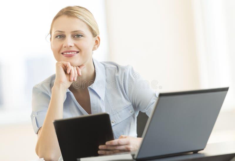 Коммерсантка с рукой на Chin держа таблетку цифров в офисе стоковые изображения rf