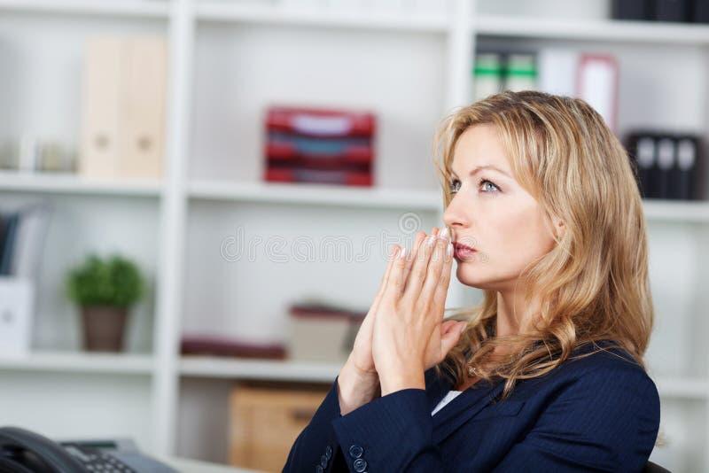 Коммерсантка с смотреть сжиманный руками прочь в офисе стоковое изображение rf