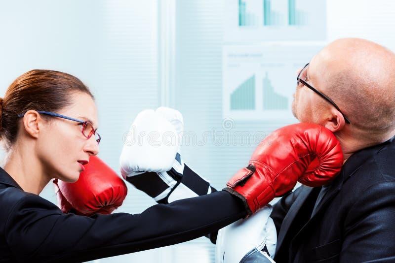 Коммерсантка ударяя сторону ` s бизнесмена с пуншем стоковое фото rf