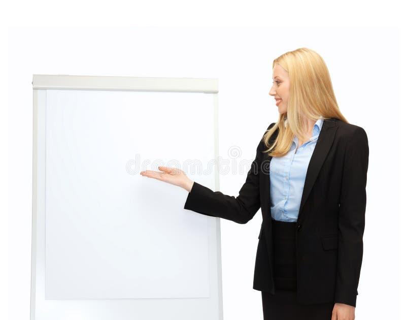 Коммерсантка указывая на белое пустое flipchart стоковые изображения