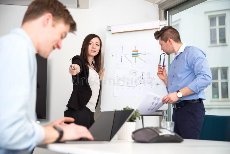 Коммерсантка указывая на мужской коллегу используя компьтер-книжку стоковое фото rf