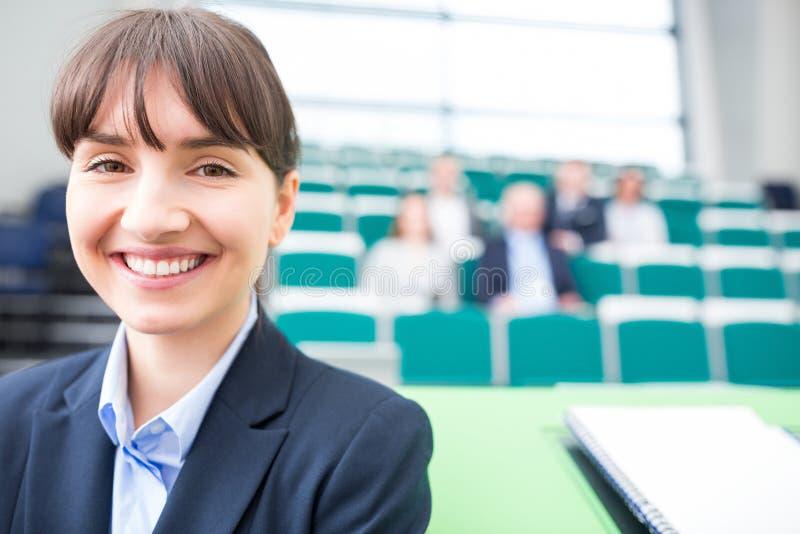 Коммерсантка усмехаясь в лекционном зале стоковое фото rf