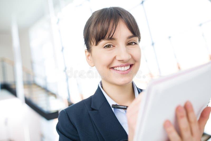 Коммерсантка усмехаясь пока пишущ на документе в офисе стоковые фотографии rf