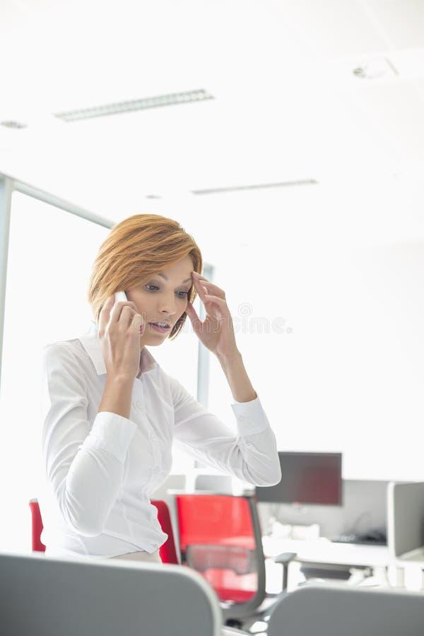 Коммерсантка удара используя сотовый телефон в офисе стоковые изображения