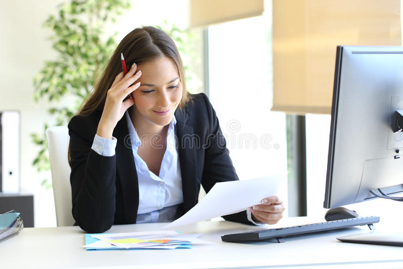 Коммерсантка читая документ стоковое фото