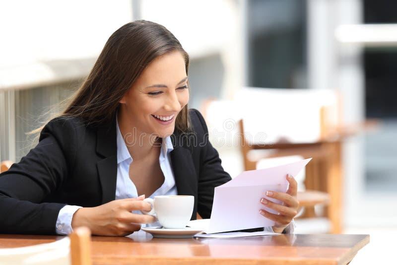 Коммерсантка читая письмо в кофейне стоковая фотография