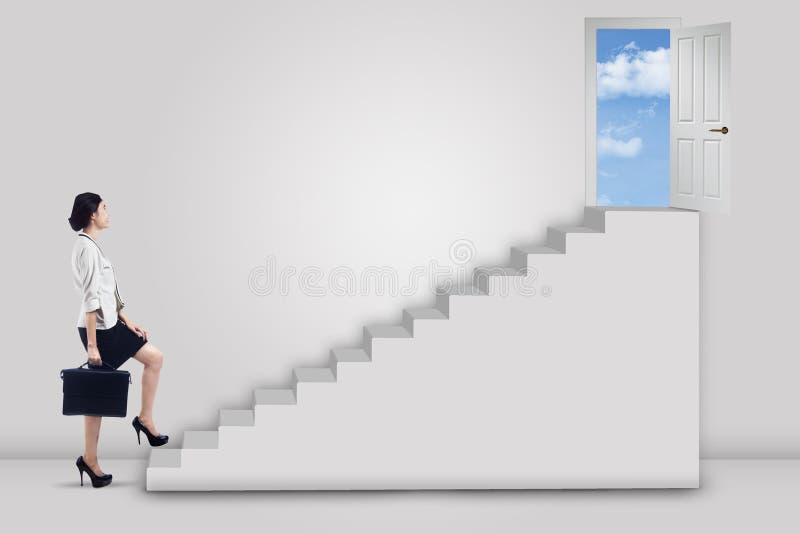Коммерсантка шагая вверх лестница к двери успеха стоковое фото rf
