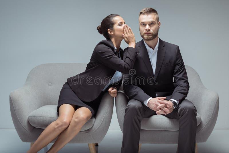 Коммерсантка шепча что-то на ухе ` s коллеги пока сидящ на стульях стоковое изображение rf
