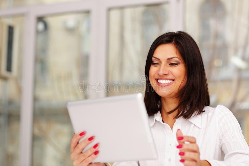 Коммерсантка Laughting держа планшет стоковые изображения