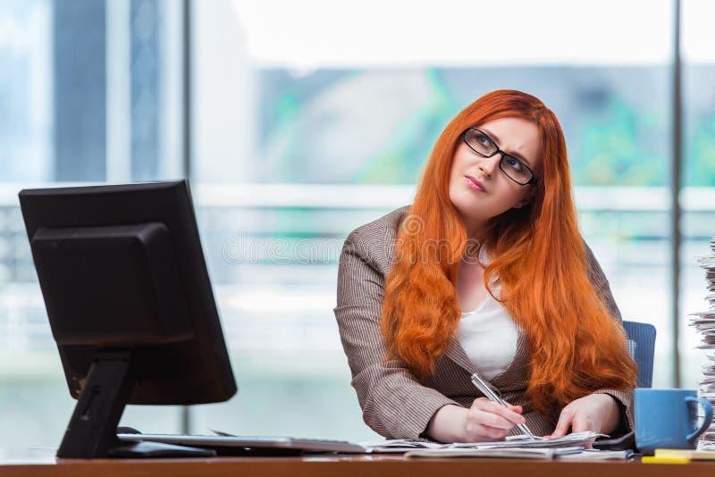 Коммерсантка redhead сидя на ее столе в офисе стоковые фотографии rf