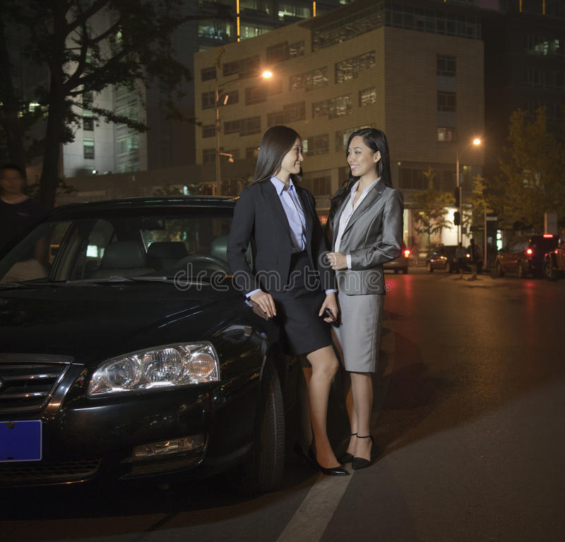 2 коммерсантки говоря автомобилем стоковое изображение
