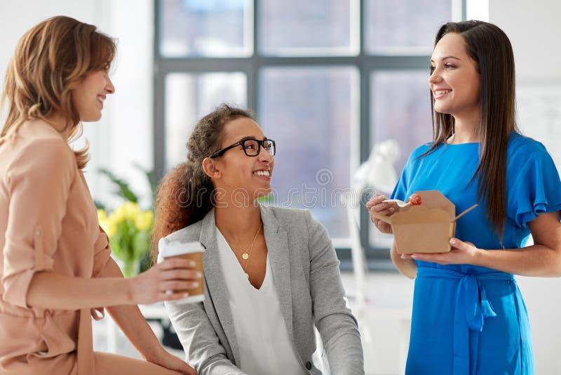 Коммерсантки имея обед на офисе стоковая фотография