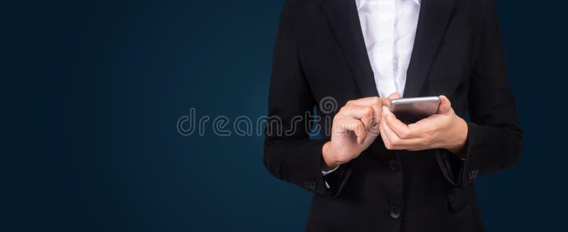 Коммерсантки портрета молодые в черном костюме используя smartphone, pre стоковое изображение