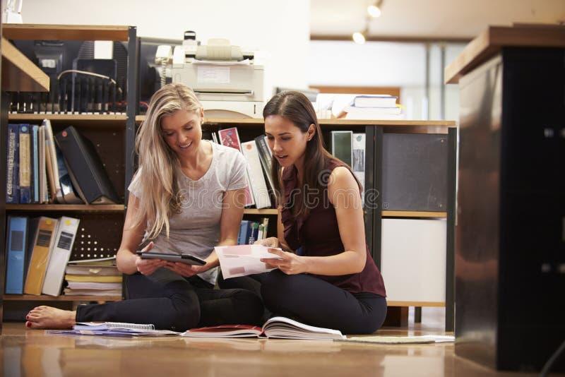 2 коммерсантки сидят на поле офиса с таблеткой цифров стоковое фото