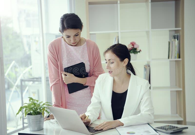 Коммерческий директор и секретарша посоветовать со для работы в офисе стоковая фотография