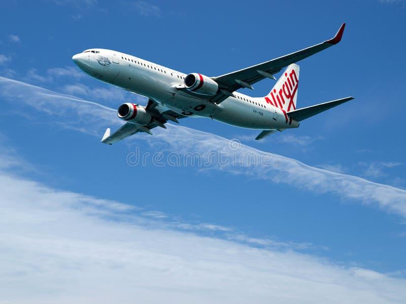 Коммерческий самолет в полете с облаком цирруса в голубом небе Aus стоковые изображения